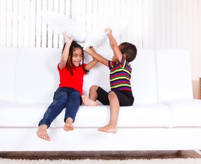 Kids playing with pillows on couch