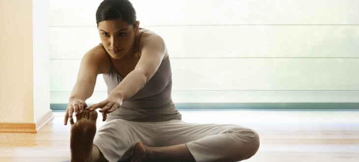 Woman sitting on floor stretching leg