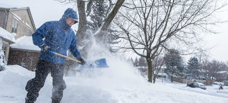 Man shovelling snow in driveway