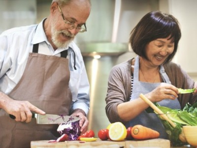 Couple chopping vegetables in kitchen