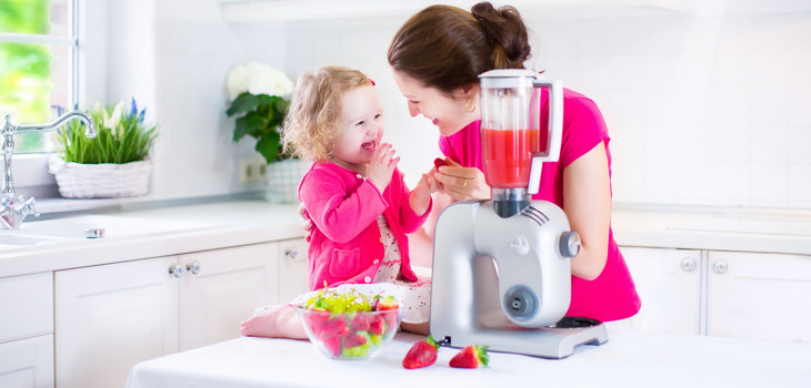 Mom and daughter making smoothies in kitchen