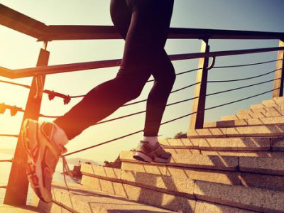 healthy lifestyle sports woman running up on stone stairs sunrise seaside
