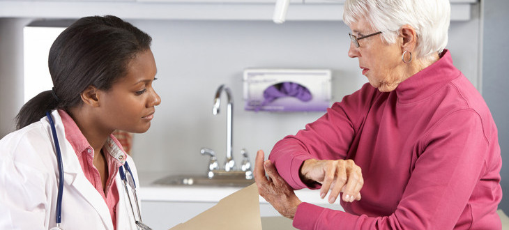 Doctor examining elderly female patient with elbow pain