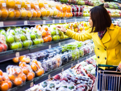 Young woman shopping for fruit in grocery store