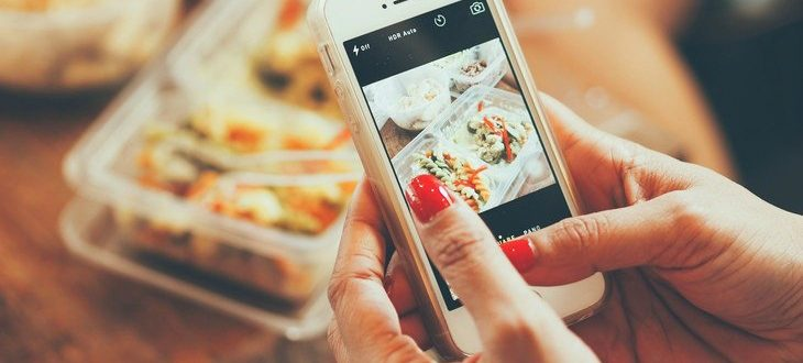 Woman photographing food with phone