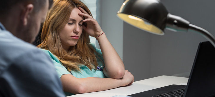 Young nurse tired holding head, shift work
