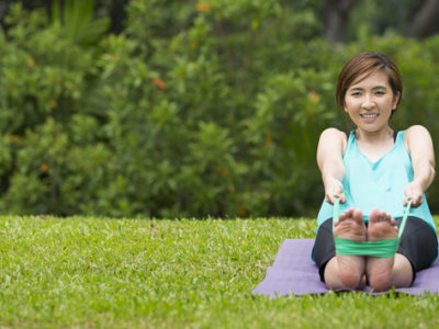 Athletic Asian woman exercising in park with fitness band