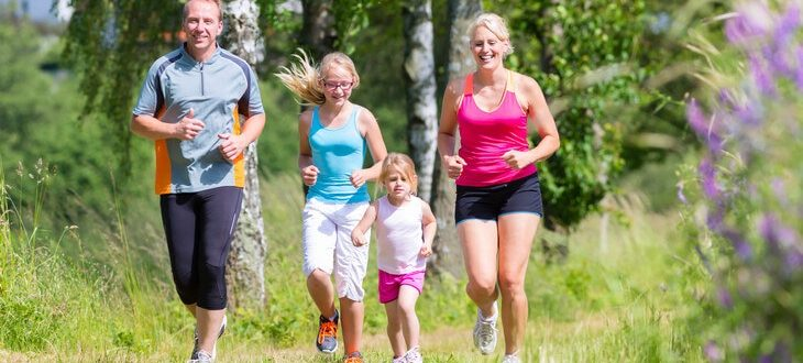 Parents with children sport running together through forest