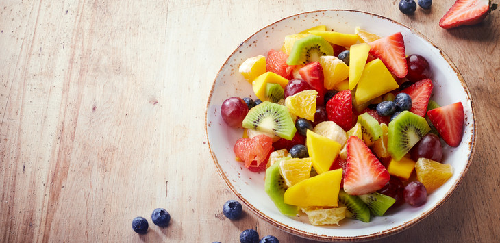 Bowl of healthy fresh fruit salad on wooden background