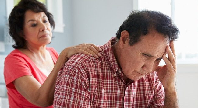 Wife comforting senior husband suffering from dementia