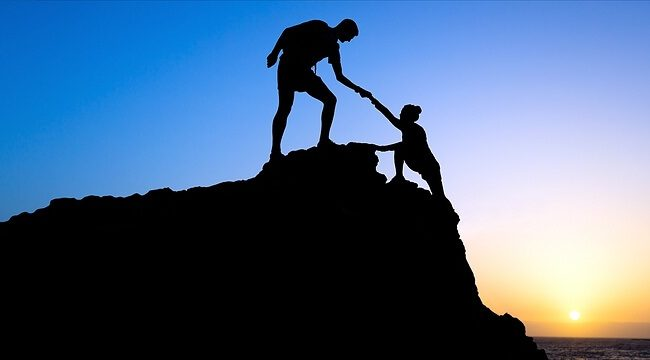 Teamwork Male and woman hiker helping each other on top of mountain climbing team, beautiful sunset landscape.