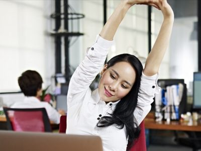 businesswoman looking at work on laptop computer stretching arms in the air.
