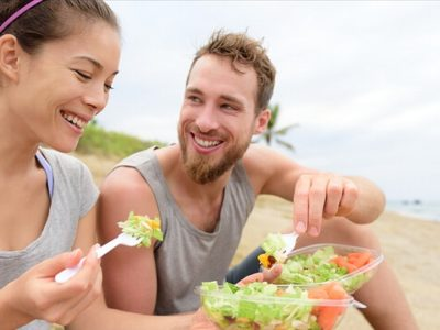 Young couple eating salad on beach