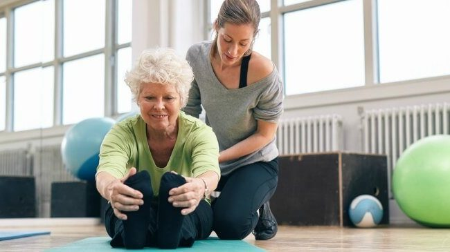 Woman stretching on floor with personal trainer