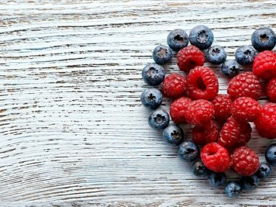Heart-shaped-raspberries-and-blueberries-on-old-wooden-background