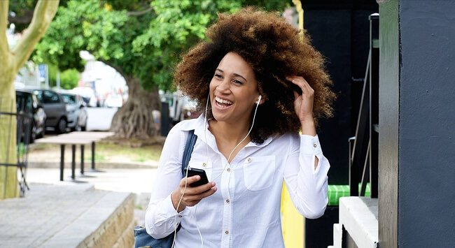 Portrait of young woman smiling with earphones and smart phone