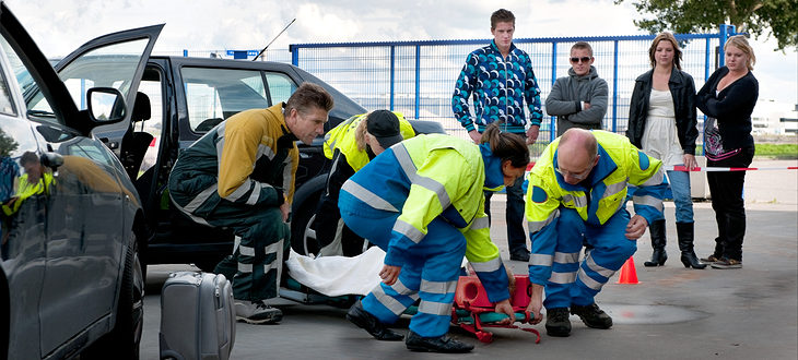 A team of emergency medical services at work, lifting an injured woman on a stretcher, to carry her away