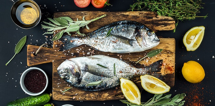 fresh-uncooked-dorado-or-sea-bream-fish-with-lemon-herbs-oil-vegetables-and-spices-on-rustic-wooden-board-over-black-backdrop-top-view