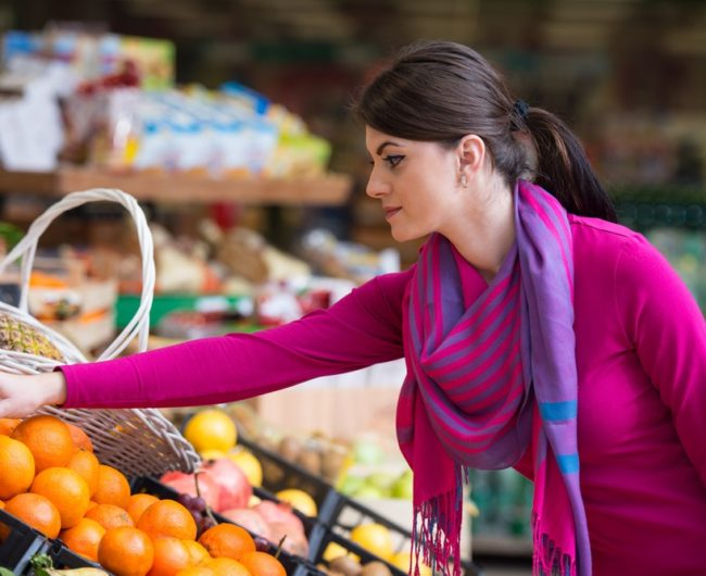 woman-picking-oranges-in-grocery-store