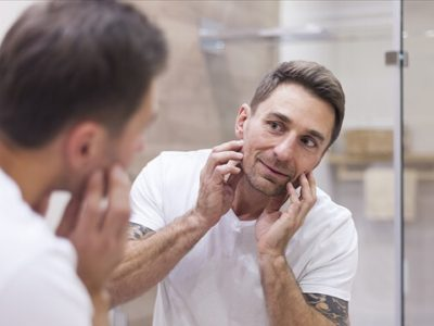 man-checking-the-condition-of-his-skin-in-mirror