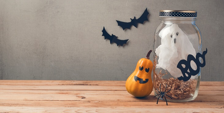 halloween-holiday-decoration-with-ghost-in-jar-and-pumpkin-with-scary-face-on-wooden-table