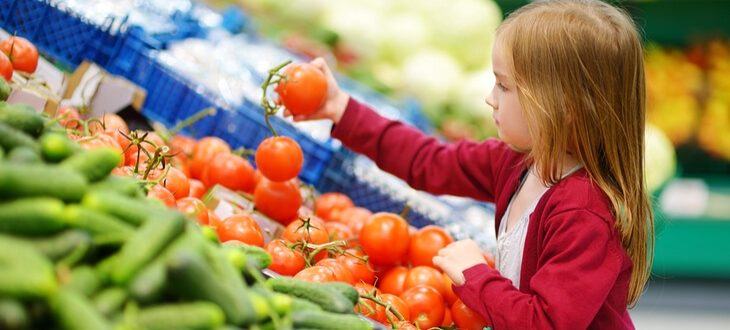 little-girl-choosing-tomatoes-in-a-supermarket