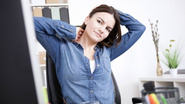Woman stretching her neck at her desk
